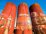 Weathered, red, big metal tanks pained as Mexican food cans, Helm, California.