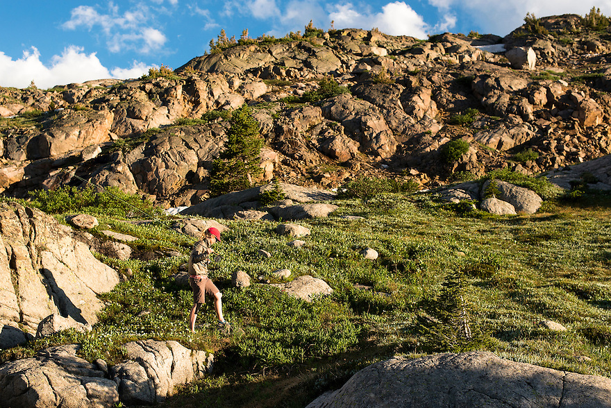 An angler hikes along a hillside in the Absaroka-Beartooth Wilderness.