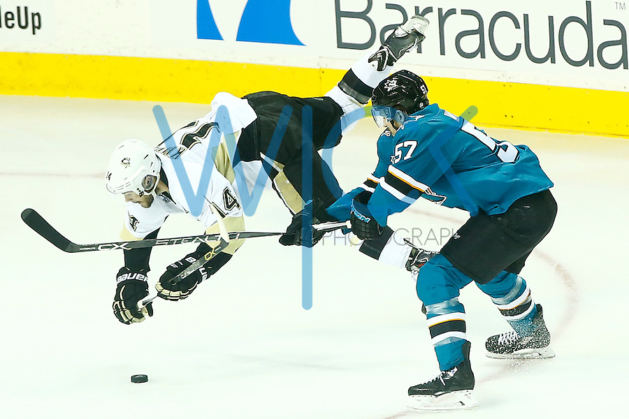 Chris Kunitz #14 of the Pittsburgh Penguins goes airborne in front of Tommy Wingels #57 of the San Jose Sharks in the second period during game three of the Stanley Cup Final at the SAP Center in San Jose, California on June 4, 2016. (Photo by Jared Wickerham / DKPS)