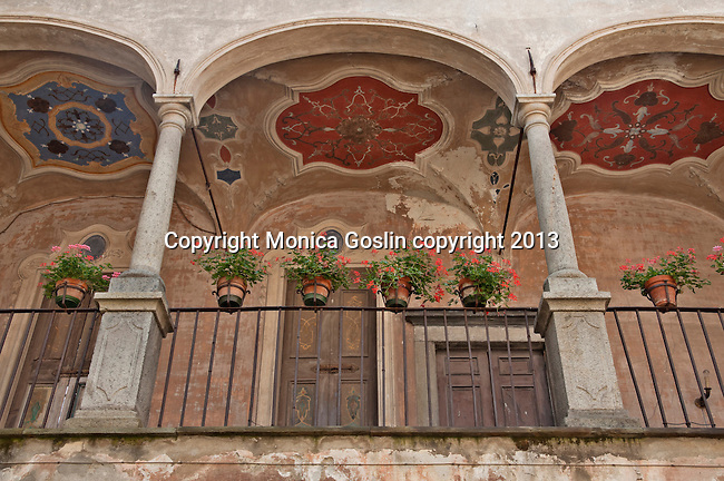 A colorful balcony with potted flowers in an old palace in Tirano, Italy