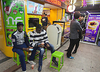 African and Chinese people are seen by a juice stall in an area of Guangzhou known to locals as 'Chocolate City', Guangzhou, Guangdong Province, China, 08 December 2014. The health authorities of Guangzhou are said to be stepping up their monitoring of the African community in light of the ongoing outbreak of the Ebola virus disease in West Africa.
