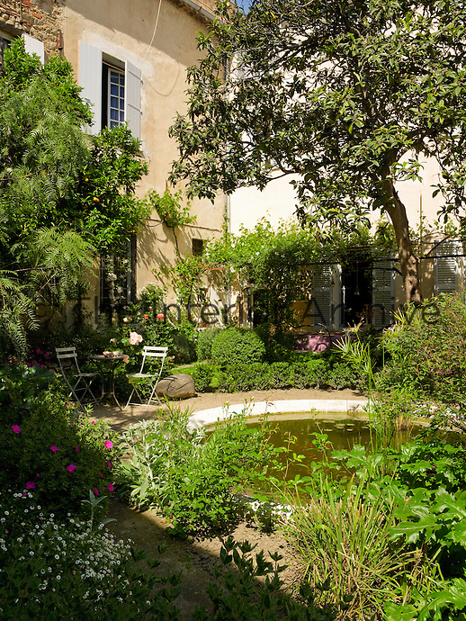The enclosed courtyard garden is designed around a central pond
