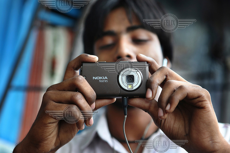 A boy taking a picture on his mobile phone in a slum surrounding Reay Road Railway Station.