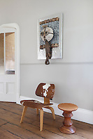 A cow-hide Eames chair in the staircase hall stands below an artwork by Zak Ove, constructed of carved wood animal parts, including a small crocodile