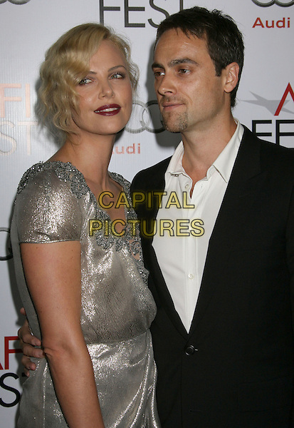 "CHARLIZE THERON & STUART TOWNSEND.The AFI Fest's Gala Screening of ""The Road"" at Grauman's Chinese Theatre in Hollywood, California, USA..November 4th 2009.half length dress wrap shiny metallic lame gold silver grey gray beaded beads neckline twenties black suit white shirt couple arm around waist.CAP/ADM/MJ.©Michael Jade/AdMedia/Capital Pictures."