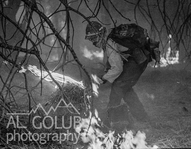 September 1, 1987 Buck Meadows, California -- Stanislaus Complex Fire -- Firefighter puts out spot fire to stop fire from running over fire camp. The Stanislaus Complex Fire consumed 28 structures and 145,980 acres.  One US Forest Service firefighter, David Ross Erickson, died from a tree-felling accident.