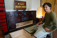 Ryoichiro Mishina of Iwayado Tansu Seisakujo showing a secret compartment in a chest of drawers, Oshu City, Iwate Prefecture, Japan, July 18, 2013. Iwayado Tansu chests of drawers have been made in the city of Oshu since the 1780s. They are noted for their fine lacquer finish and finely-wrought metalwork fittings.