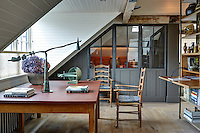 Two ladderback chairs and a wooden table occupy a space beneath the window in the study