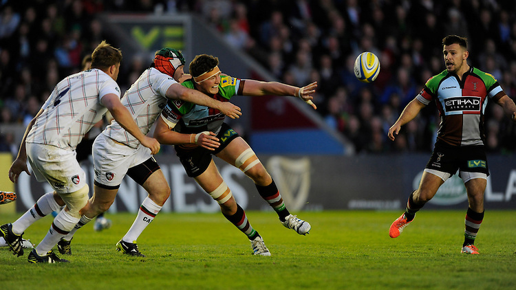 Charlie Matthews of Harlequins offloads as he is tackled by Julian Salvi of Leicester Tigers during the Aviva Premiership match between Harlequins and Leicester Tigers at the Twickenham Stoop on Friday 18th April 2014 (Photo by Rob Munro)