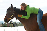 A young woman hugs her horse in Wilson, Wyoming.