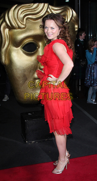 GERI HALLIWELL.The British Academy Children's Film and Television Awards, London, Hilton Hotel, Park Lane, London, England. .November 30th, 2008 .BAFTA BAFTA's full length red dress ruffles gold shoes beige satin crystals tiered layers off the shoulder platform slingbacks see through thru hand on hip.CAP/ROS.©Steve Ross/Capital Pictures.