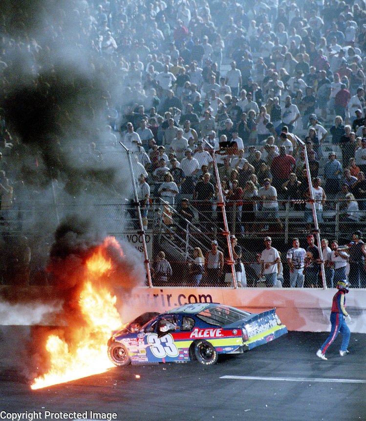 NASCAR driver Tony Raines walks away from his burning race car after crashing during a Busch Series race at Richmond, VA on Friday, 9/8/00.  (Photo by Brian Cleary)