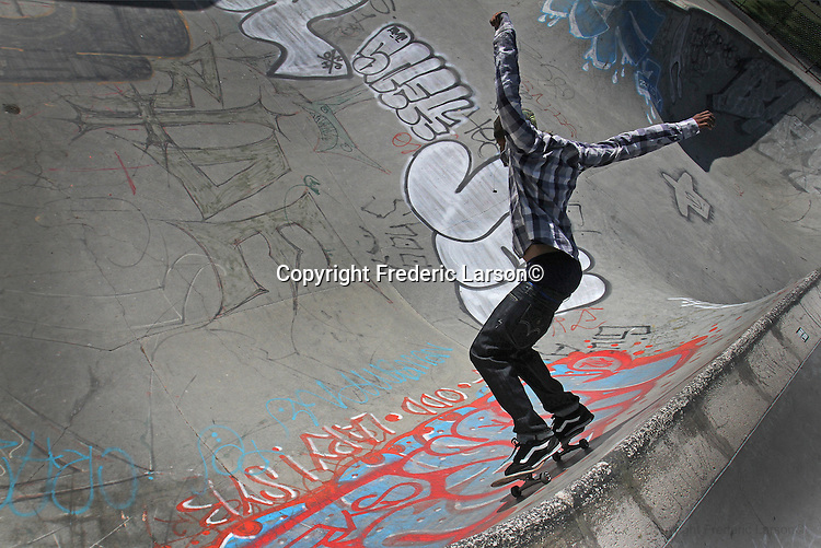 A young man does some skateboarding in a deep bowl at San Francisco Portreo del Sol/La Raza Skatepark.