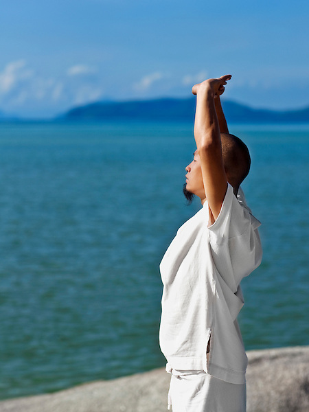 Man Practices Qi Gong at Kamalaya, Koh Samui, Thailand. Qi Gong Master Dr. Song practices morning Qi Gong by the beach at Kamalaya resort.