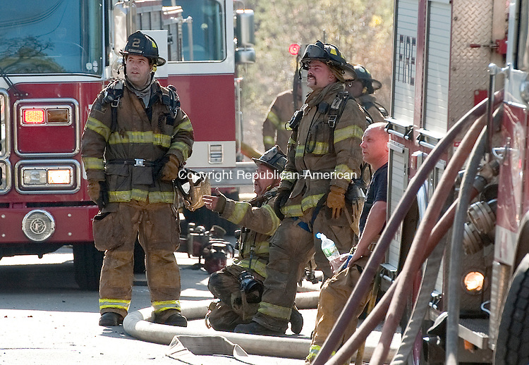 WATERBURY, CT 27 APRIL 2013--042713JS05--Waterbury firefighters look on after they were ordered out of the structure as they battled a pair of house fires on Tremont Street in the Bunker Hill section of Waterbury on Saturday. The fire started in one house and jumped to the neighboring home. . Jim Shannon Republican-American.