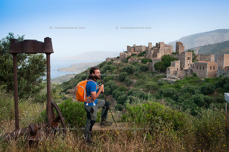Vathia, Mani, Peloponnesos, Greece, May 2013. Mountaineer Thanos, who is working on the restauration of some ancient Mani Tower houses in Vathia, guides us over the path past the temple of Poseidon down to the lighthouse at Cape Tainaron. The sizeable building, which once housed a keeper and his family, is deserted and its operation has been<br /> automated. At 36.4° latitude, you are further south than Tunis and Algiers, and only marginally further north than Tarifa, mainland Europe's southernmost point. Tankers ply past in both directions with a faint rumble.<br />  of The Peloponnese peninsula offers beautiful hikes along the bays and capes of the Mani and Monemvasia and the interior Taygetos. Venture inland, away from the crowds, and there are some surprises in store: snow-capped mountains, limestone gorges, shady rivers, crumbling castles, tower-villages, fir forests, frescoed chapels, and solated monasteries. Ancient mountain villages interrupt the olive groves that line the rugged coastline that is surrounded by deep blue and turquoise waters of the Mediterranean.  Photo by Frits Meyst/Adventure4ever.com