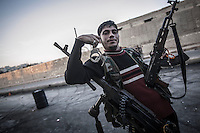 In this Sunday, Oct. 28, 2012 photo. A rebel fighter poses for photo at the Bustan Al-Pasha front line after an army jet was flying the sky and hits the rebel position at the northeast of the neighborhood in Aleppo, the Syrian's largest city. (AP Photo/Narciso Contreras).