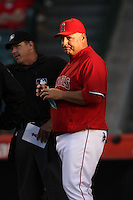 Los Angeles Angels Manager Mike Scioscia #14 meets with the umpires before a game against the San Francisco Giants at Angel Stadium on June 18, 2012 in Anaheim, California. San Francisco defeated Los Angeles 5-3. (Larry Goren/Four Seam Images)