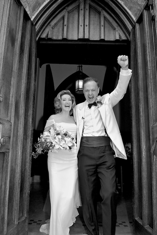 Black & white shot of an excited bride and groom exiting  the church.