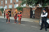 A policeman on duty watches young members of Flamboyan Carnival Arts at Notting Hill Carnival, London