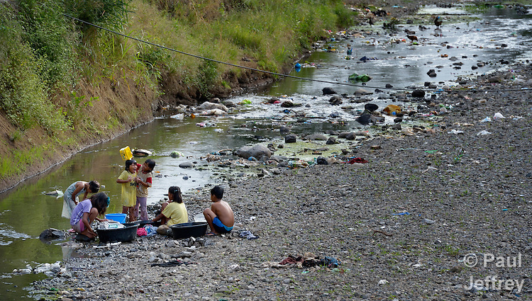 Girls bathe and wash laundry in a stream that runs through the Suburban neighborhood of Rodriguez, Rizal, in the Philippines. Most of the community's families were relocated here from other area of Manila and the nearby countryside to make way for urban renewal projects or to move them out of harm's way. Yet the new community was hit hard by Typhoon Ketsana in 2009, and Christian Aid, a member of the ACT Alliance, provided emergency relief supplies. Over the years since, with help from Christian Aid and other groups, community members have organized themselves and engaged in a process of disaster risk reduction, including identifying and mapping high-risk zones and evacuation routes in their area. Christian Aid has also assisted with financial and technical support for income generating livelihood projects and community enterprises.