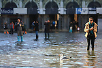 Tourist walk with boots and plastic bags to protect their shoes on flooded St Mark's square during an acqua alta (high-water). The Acqua Alta, a convergence of high tides and a strong sirocco, reached 125 centimetres in Venice, on November 20, 2013.  <br /> <br /> &copy; Pierre Teyssot