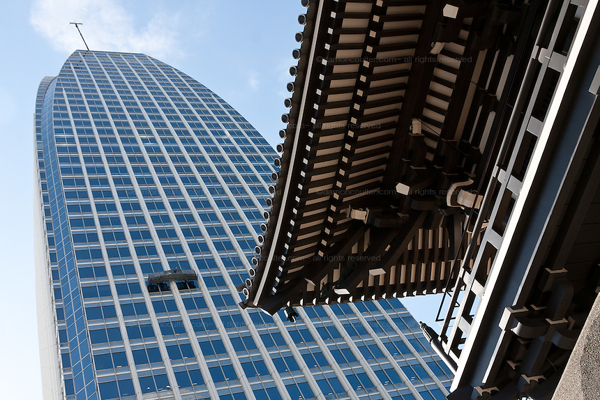Window cleaners in a cradle on an office tower above a shrine in Tokyo, Japan. Friday February 3rd 2012