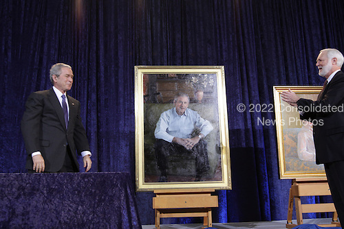 Washington, DC - December 19, 2008 -- United States President George W. Bush unveils his National Portrait Gallery portrait along with the Secretary of the Smithsonian Institution, G. Wayne Clough, right, at the National Portrait Gallery in Washington, DC, on Friday, December 19, 2008. The painting is by Robert Anderson.  .Credit: Ken Cedeno / Pool via CNP