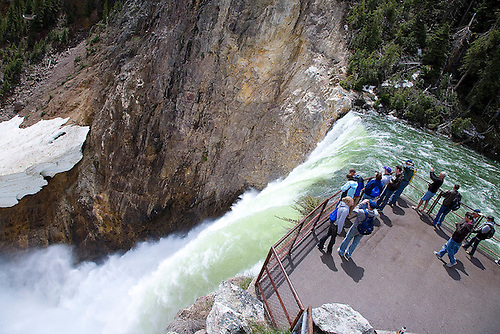 TOURISTS GATHER AT A VIEWING AREA ON THE BRINK OF THE LOWER YELLOWSTONE FALLS IN YELLOWSTONE NATIONAL PARK,WYOMING