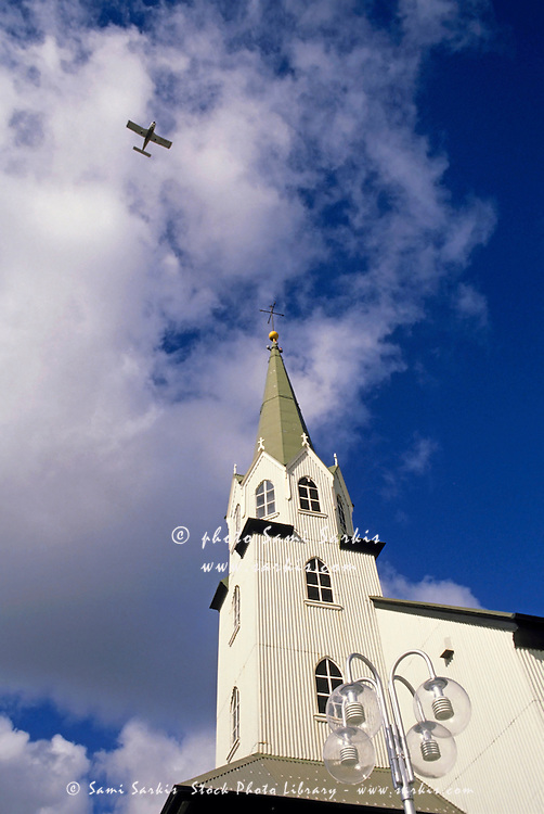 Church tower with view of plane flying overhead in a cloudy sky, Reykjavik, Iceland.