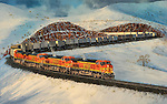 "Mountain railroading in the high Sierras on Christmas Day, BNSF units letting a container train run a  downhill slope. Oil on canvas, 23.5"" x 37""."