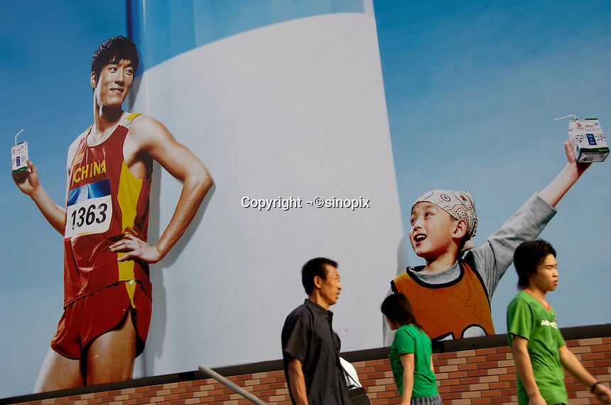 Chinese pedestrians walk past a billboard featuring Olympic champion Liu Xiang promoting a brand of milk in Beijing, China. Liu Xiang became a Chinese hero and idol after he won the 110-metre hurdles at the Athens Olympics Games..