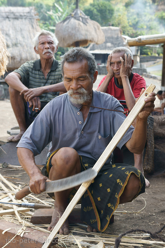 elder villager Franziskus helps in finishing the roof of a house as part of sacred celebrations of buidling a house, center of matriarchal society of Ngada people, village Bena near Bajawa,  Flores, Indonesia