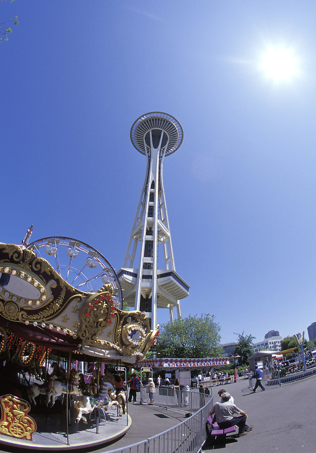 Looking up at Seattle Space Needle above a merry-go-round in the Fun Forest, Seattle, Washington