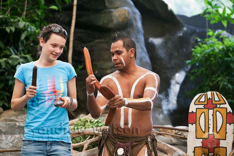 Indigenous performer teaching tourist to dance at Tjapukai Aboriginal Cultural Park.  Smithfield, Cairns, Queensland, Australia