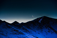 The waning crescent Moon sets over 13,427 foot high Grizzly Peak in Colorado, just as the Sun's first ray's illuminate the snow line on her ridges.