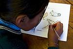 School girl coloring Andean cat during an educational outreach program, Ciudad de Piedra, Andes, western Bolivia