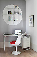 A small study area with an Eero Saarinen chair and a circular shelving disc