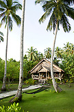 INDONESIA, Mentawai Islands, Kandui Surf Resort, exterior of a guest cabin at Kandui resort with lawn and palm trees