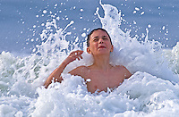 Young boy splashes in an ocean wave...