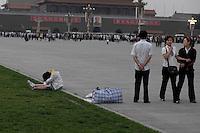 Un couple de migrants perdus sur la place. Ils ont posé leur sac. La jeune fille s'est endormie, son compagnon est resté debout à contempler le portrait de Mao sans bouger. Un soir place Tiananmen, mai 2009.