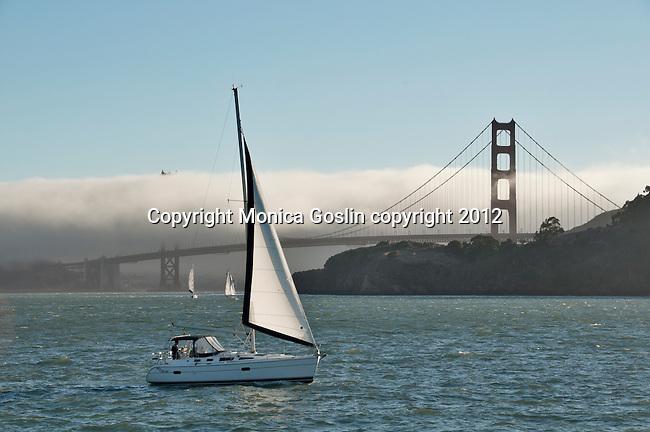 Golden Gate Bridge in San Francisco, California with fog and sailboats