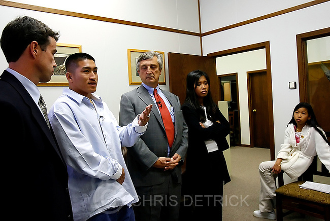 Salt Lake City, Utah --10/31/2005--4:43:22 PM.Steve Ousa, the son Bounmy Ousa, speaks at a press conference, with his joint attorneys Ted McBride, far left, and Clark Newhall, center.  Bounmy Ousa's daughter Chanhda and her daughter Shauna, 11, are at right. ..A press conference will be held in the law office of a man representing the family of Bounmy Ousa, who was fatally shot in West Valley City in July. The District Attorney's Office has cleared the officers involved.....Photo by: Chris Detrick/The Salt Lake Tribune.File #_K2O9683
