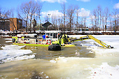 An amphibious excavator braking ice on L'Assomption river in Joliette Quebec, to prevent ice jams and flooding.