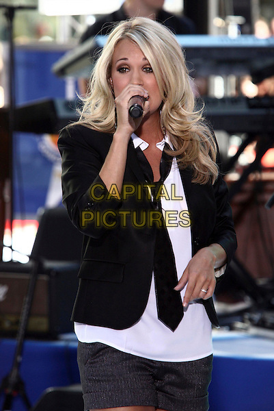 "CARRIE UNDERWOOD.performs live on the NBC's ""TODAY"" Show live from Rockefeller Center, New York, NY, USA, 30th July 2010..music country live on stage concert gig.half length  black jacket blazer white shirt tie microphone singing hand wedding ring .CAP/ADM/PZ.©Paul Zimmerman/AdMedia/Capital Pictures."