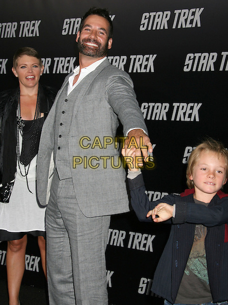"NATALIE MAINES, ADRIAN PASDAR & JACK.""Star Trek"" Los Angeles Premiere held at Grauman's Chinese Theatre, Hollywood, CA, USA..April 30th, 2009.half 3/4 length black dress grey gray suit white waistcoat son beard facial hair married husband wife couple mother father mom mum family jacket necklaces jeans denim holding hands .CAP/ADM/MJ.©Michael Jade/AdMedia/Capital Pictures."