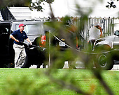 United States Senator Lindsey Graham (Republican of South Carolina), far left, carries one of his golf clubs as he leaves the presidential limo following a round of golf with US President Donald J. Trump who can be seen at the far right talking on the phone as he enters the White House in Washington, DC on Saturday, October 14, 2017.<br /> Credit: Ron Sachs / Pool via CNP