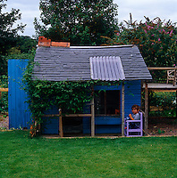 Joe sits on the porch of the blue Wendy house at the end of the garden