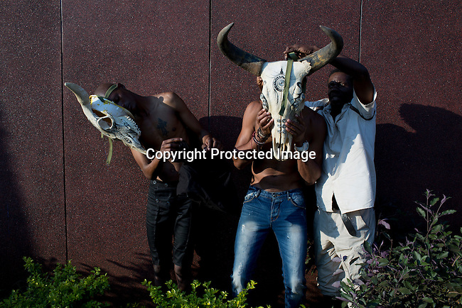 HARARE, ZIMBABWE - SEPTEMBER 27: The Zimbabwean artist Shorai fits two male models with his cattle head pieces before a show a fashion show on September 27, 2014 at the Harare City library in Harare, Zimbabwe. Local and African and based designers showed their collections during the 5th edition of Zimbabwe Fashion week (Photo by: Per-Anders Pettersson)