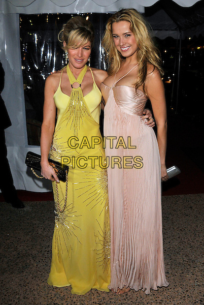 HOFIT GOLAN & PETRA NEMCOVA.Arriving for a party on designer Roberto Cavalli's boat during the 61st Cannes International Film Festival, Cannes, France, May 21st 2008..full length yellow dress pale pink peach halterneck pleated clutch bag .CAP/PL.©Phil Loftus/Capital Pictures